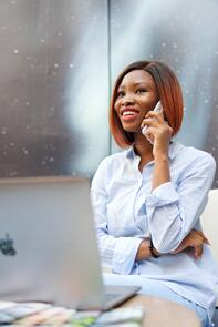 Image of a businesswoman or merchant on the phone looking happy